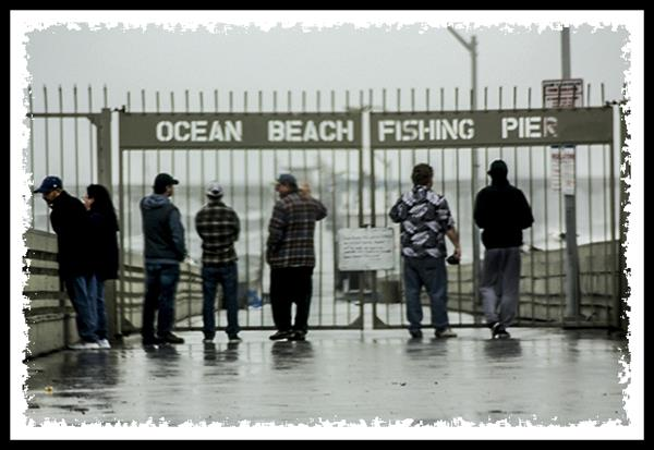 Gawkers watching the waves at Ocean Beach Pier during storm